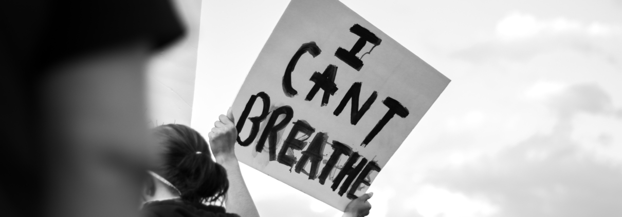"""Female protester holding up a sign that says """"I CAN'T BREATHE"""""""