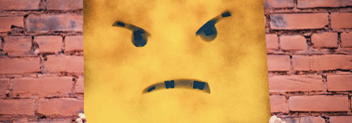Poster of a frowning yellow cartoon face, held up by two hands.