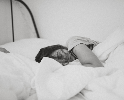 Woman curled up sleeping in a bed of white sheets and pillows